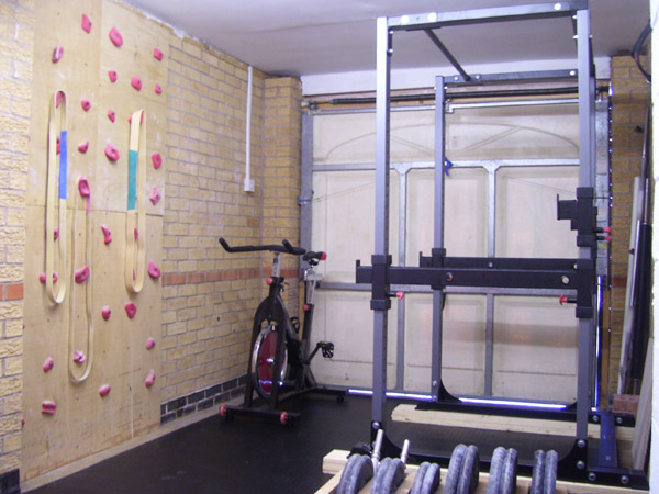 A garage gym with a rock climbing wall