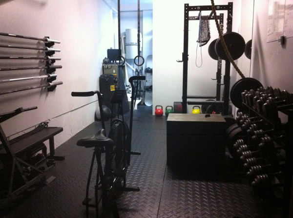 Sweet garage gym - tight quarters but nice flooring, dumbbells, even air dyne