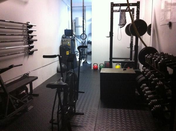 Sweet garage gym - tight quarters but nice flooring, dumbbells, even air dyne