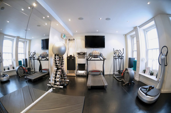 Fish eye lens photo of a home gym with ample cardio equipment, nice dumbbell selection and great lighting