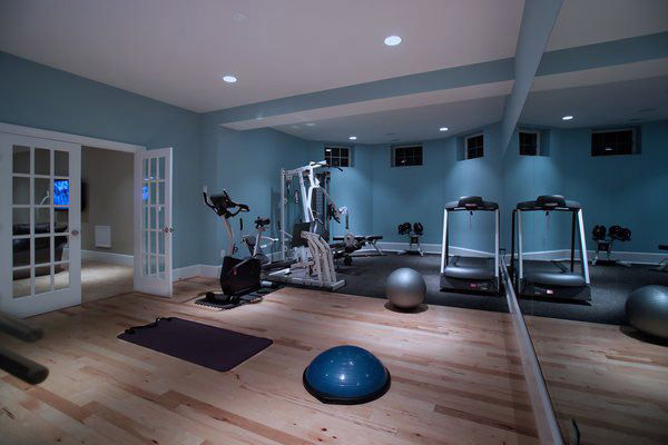 Nice den conversion into a home gym with weight gear, cardio, and core training