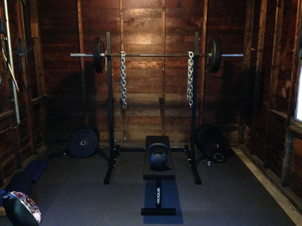 Simple one car garage gym - squat stand, bumpers, bench, kettle. WOD away