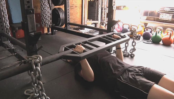 Floor presses with a Swiss bar using chains instead of plates for dynamic lifting