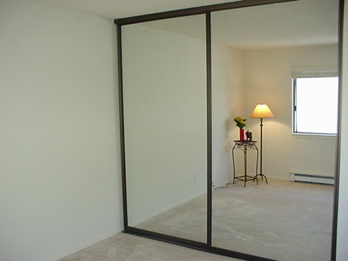 Sliding closet doors with large vanity mirrors - Remove the frame and you have one giant mirror for your garage gym