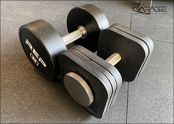 50-lb round, commercial-grade dumbbells next to a 50-lb Ironmaster Quick Lock Dumbbell